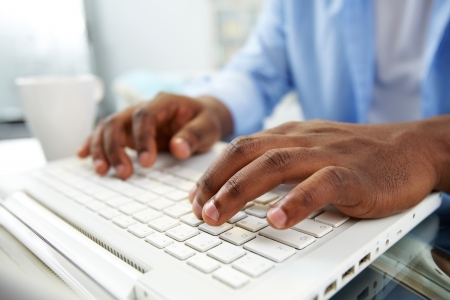 Close-up of African man typing on laptop Stock Photo - 13949199