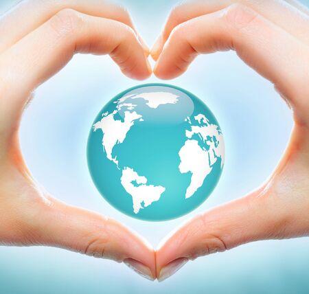 mundo manos: Imagen de Creative del modelo de la tierra dentro del coraz�n formado por manos humanas