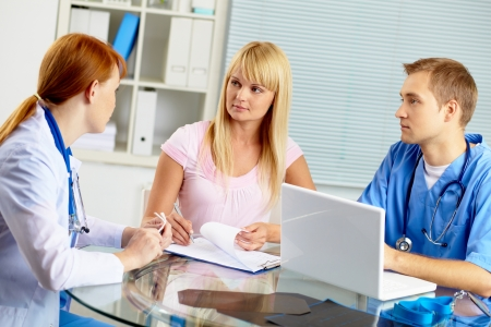 practitioner: Portrait of confident practitioner consulting patient in hospital Stock Photo
