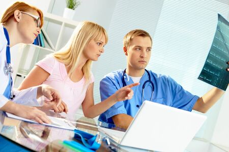 Portrait of two doctors and young woman reading x-ray in hospital photo