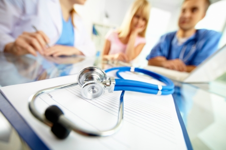 consultant physicians: Close-up of stethoscope and paper on background of doctors and patient working with laptop Stock Photo