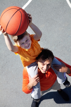 sporting activity: Image of young man and his son playing basketball