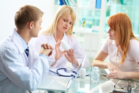 Portrait of confident practitioner prescribing vitamins to patient in hospital photo