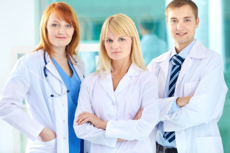 healthcare team: Portrait of three clinicians in white coats looking at camera