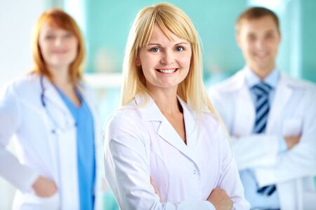 clinician: Portrait of pretty clinician in white coat looking at camera with smile
