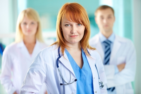 white coat: Portrait of pretty clinician in white coat looking at camera with smile
