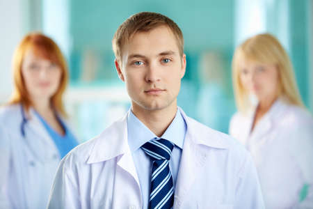 clinician: Portrait of serious clinician in white coat looking at camera