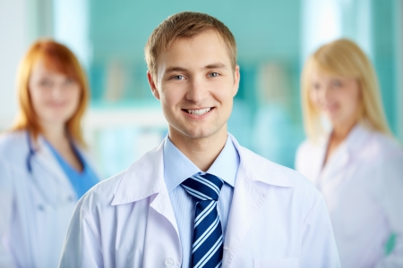 Portrait of handsome doctor in white coat looking at camera photo