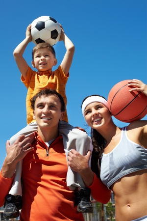 sporting: Portrait of happy family holding balls outside