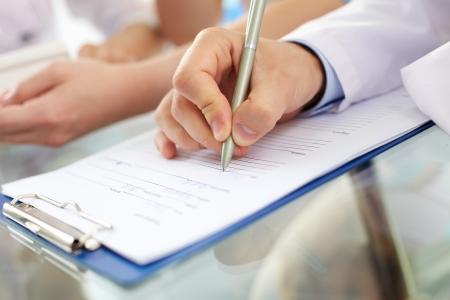 Hand van arts met een pen schrijven op recept blanco
