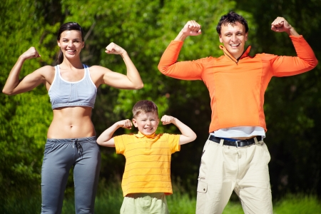 Portrait of family of three showing their strength