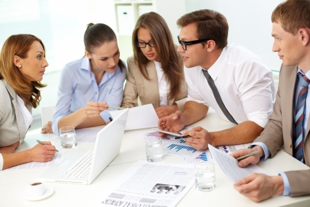 subordinates: Business team of five holding a briefing to discuss the latest ideas concerning the project Stock Photo