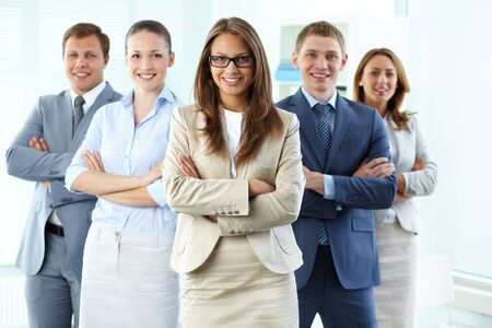 Confident business team with a female leader looking at camera and smiling Stock Photo - 13949827
