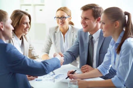 trust people: Partners concluding deal and shaking hands in the presence of team members Stock Photo