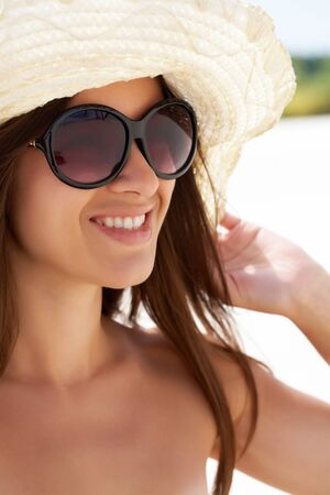 Vertical shot of a smiling girl wearing summer hat and sunglasses Stock Photo - 13949829