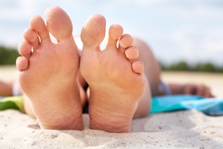 sandy feet: Close-up of a female lying on beach barefoot