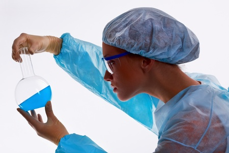 Young female scientist looking at fluid specimen, isolated against white background photo