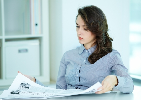 reading news: Serious business woman looking through newspaper at her workplace