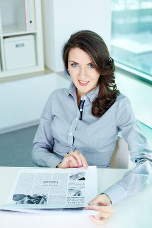 Vertical shot of a pretty business lady in her office looking at camera and smiling photo