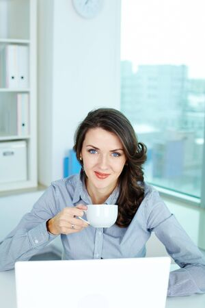 Vertical portrait of a lovely office girl holding a cup of coffee and smiling at camera photo