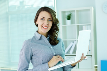 Business girl with laptop smiling at camera photo