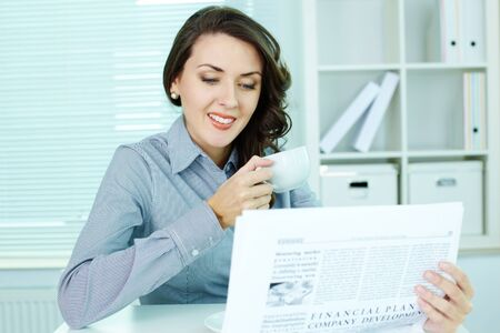 Office girl reading newspaper and smiling reading good news photo