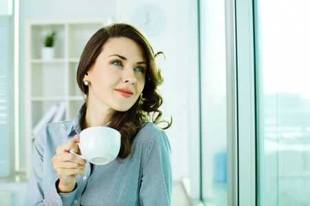 Image of a happy business woman enjoying the coffee-break photo