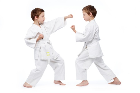 Little twins in uniform practicing judo, isolated on white photo