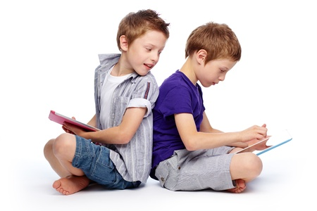 twins: Boys sitting back to back using hi-tech digital pads Stock Photo