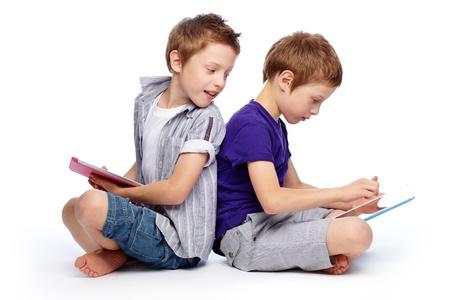 twins: Boys sitting back to back using hi-tech digital pads Stock Photo
