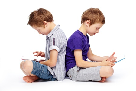 gadget: Cute twins sitting back to back and exploring the possibilities of modern technologies