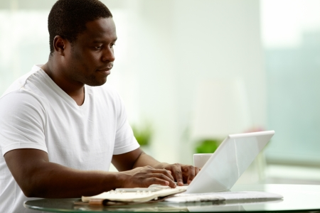 Image of young African man typing on laptop at home Stock Photo - 14056945