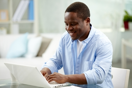 Image of young African man typing on laptop photo