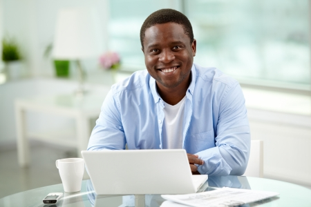 Image of young African man looking at camera with laptop near by photo