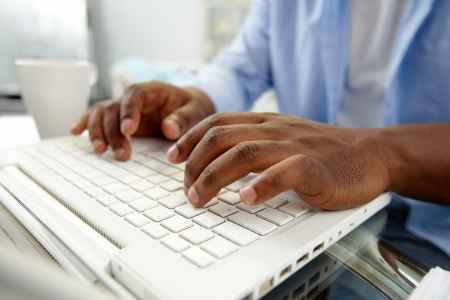 Close-up of African man typing on laptop Stock Photo - 14056990