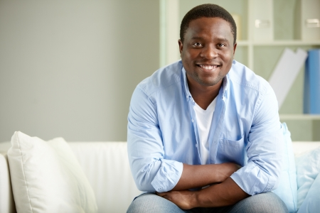Image of young African man sitting on sofa and looking at camera photo