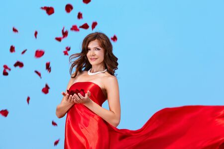 Portrait of charming female in elegant red dress holding rose petals photo