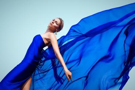 avantegarde: Photo of graceful female folded in dark blue chiffon shawl looking at camera Stock Photo