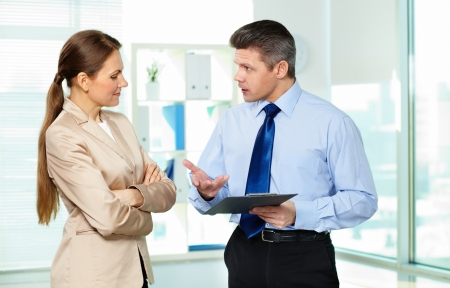 businessman standing: Formally dressed young people discussing papers in office