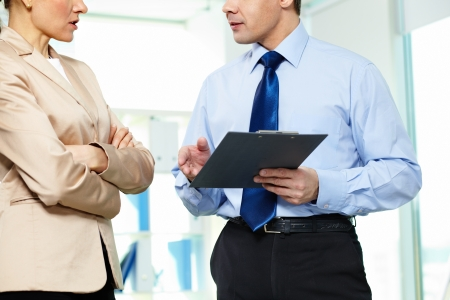 Formally dressed business partners discussing papers in office photo