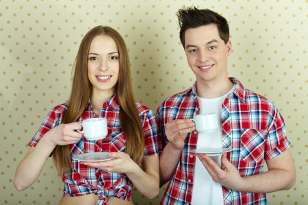 Young couple with cups and saucers looking at camera and smiling Stock Photo - 14057091