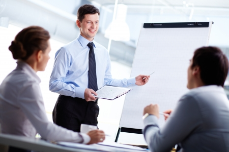 Confident businessman and his partners discussing something on a whiteboard Stock Photo - 14057039