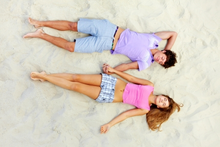Above angle of two teenage friends lying on sandy beach and holding by hands photo