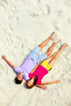 Above angle of two teenage friends lying on sandy beach with closed eyes photo