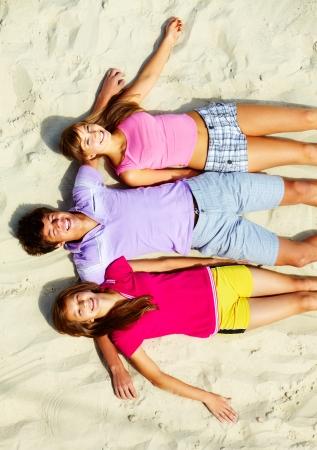 Above angle of happy teenage friends lying on sandy beach photo
