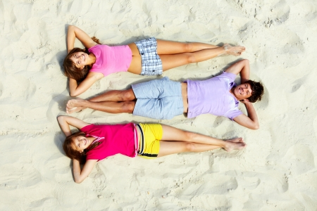 barefoot teens: Above angle of relaxed teenage friends lying on sandy beach