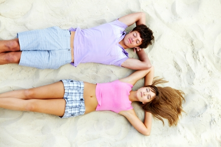 guy on beach: Above angle of teenage couple relaxing on sandy beach