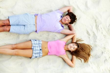 pareja durmiendo: Por encima del �ngulo de la pareja de adolescentes de relax en playa de arena