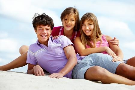 companionship: Retrato de tres amigos adolescentes en playa de arena