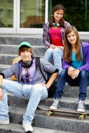teenage girl happy: Portrait of happy teens on stairs looking at camera Stock Photo